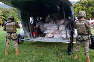 Marines guard packages of white powder seized yesterday from a boat in Guerrero.