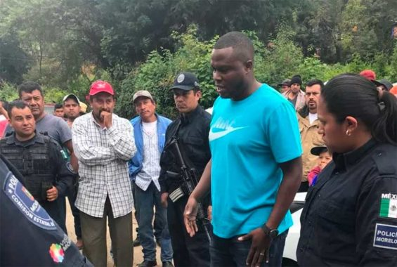 Police look on as Colombian citizen Lozano, accused of extortion, speaks with residents. They lynched him shortly after.