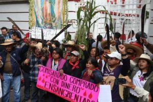 Airport protesters raise their machetes in defiance against the project.