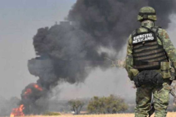 A soldier watches as a fire burns at a tap on the Tula-Salamanca pipeline in Guanajuato.