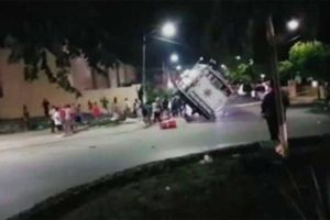 Residents push over a mobile police unit in Playa del Carmen last night.