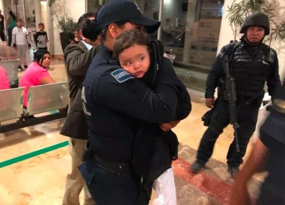 Mya Fernanada in the arms of a police officer after her rescue yesterday.