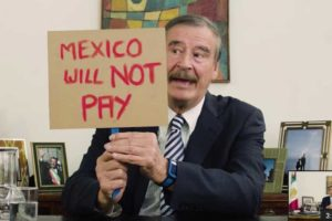 Vicente Fox holds a sign bearing a message for Trump regarding the border wall.