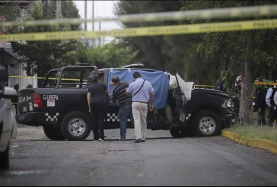 Investigators at the scene of yesterday's shooting in which four police officers died.