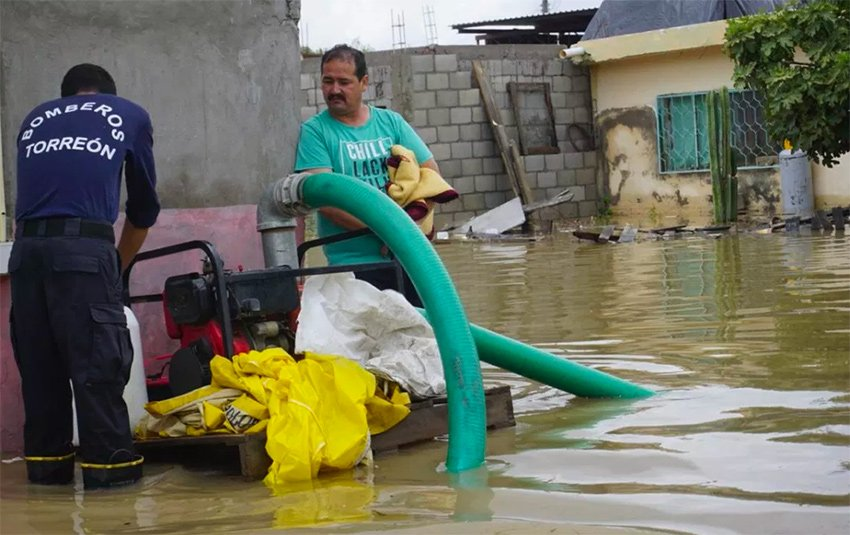A Torreón firefighter mans a pump to remove floodwaters.