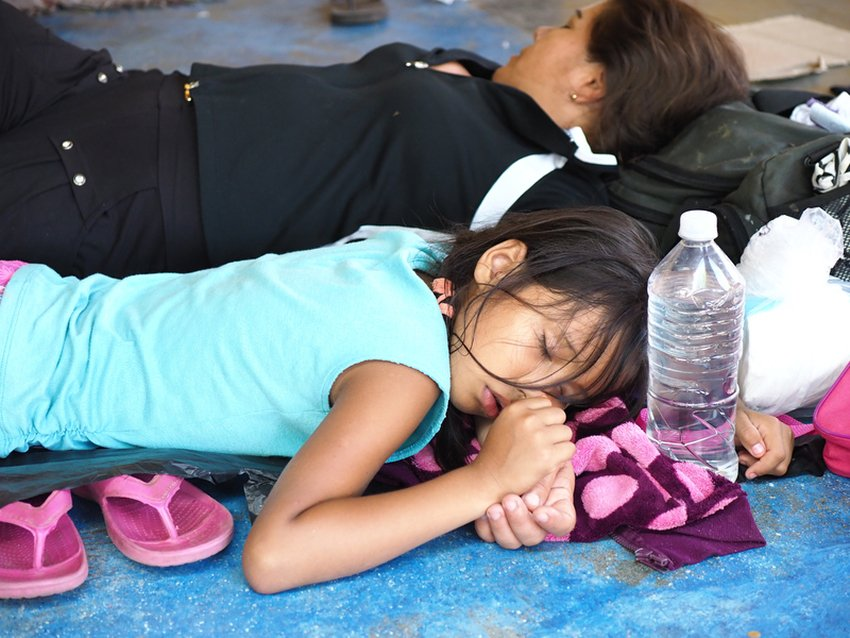 A child rests with her mother in a school that had been converted into a refuge for women and children.