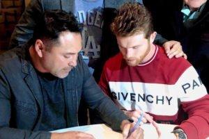 Boxer Álvarez, right, signs his new contract.