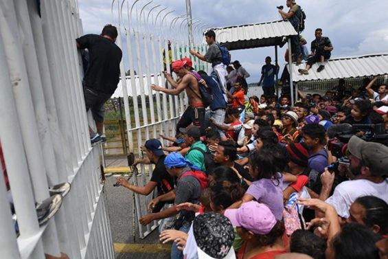 Central American migrants break through a gate on a bridge at the Guatemala border yesterday.