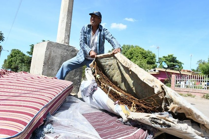 A Culiacán man shows his used mattress with the cover removed. One resident said they weren't fit for dogs to sleep on.