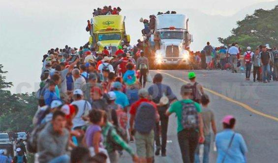 Migrants climb aboard semis as they head for Juchitán.