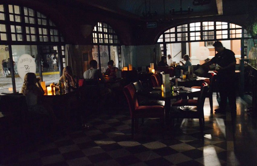 Patrons dine by candlelight in a Mérida restaurant during electricity rates protest.