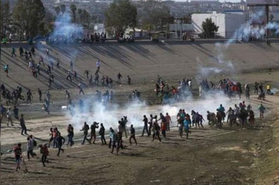 Migrants rush the border yesterday in Tijuana.