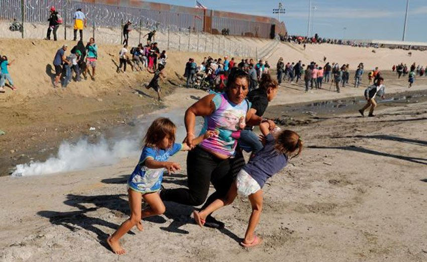 A widely shared photo of a Honduran family fleeing the tear gas at the US border on Sunday