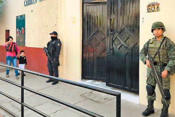 A police officer and a soldier stand guard at a Guerrero school.