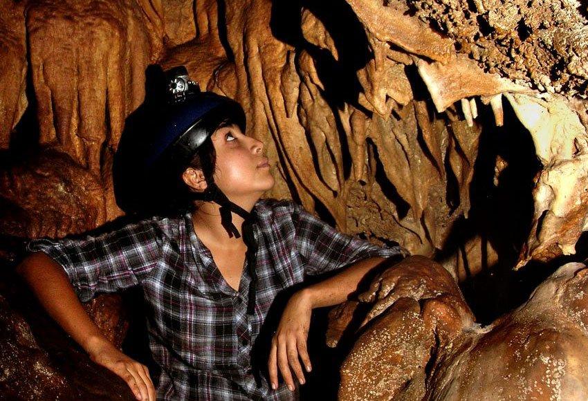 Lluvia Ramírez admires cave draperies.