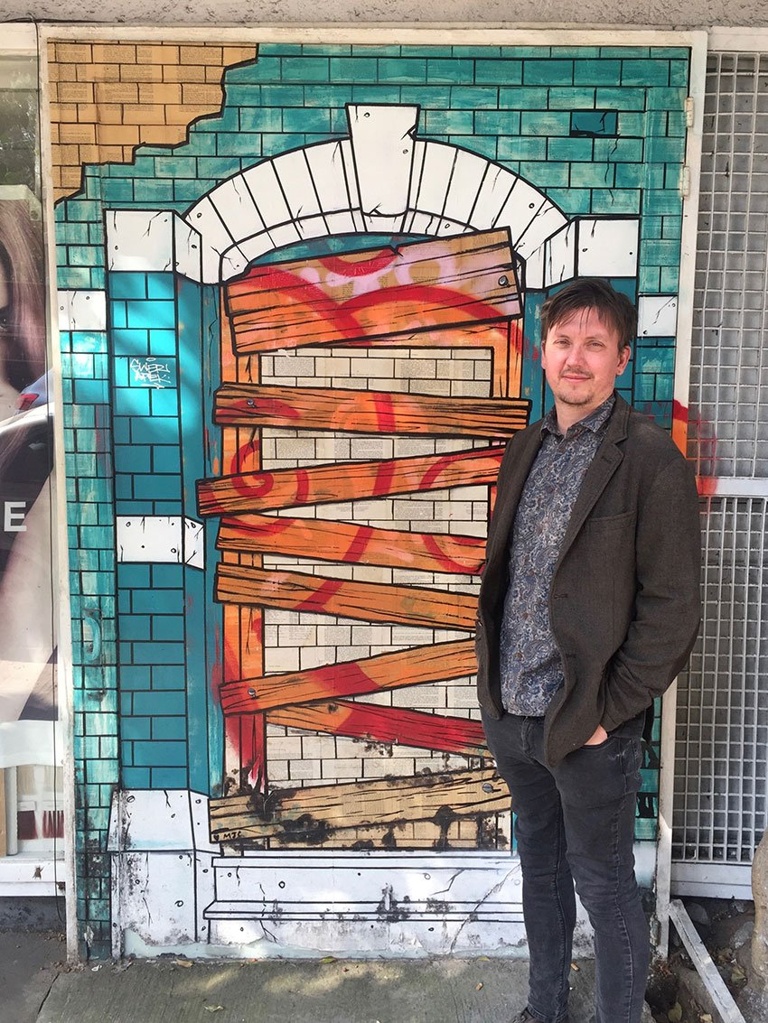 The artist in front of his mural in the Roma Norte neighborhood.