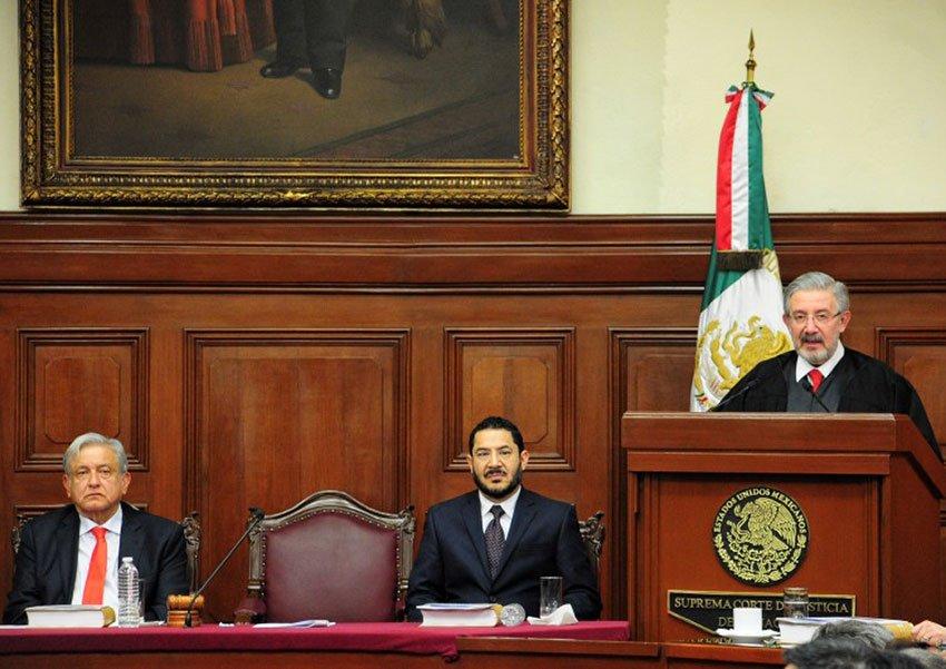 López Obrador and Morena party Deputy Martí Batres listen as Supreme Court justice Aguilar gives his address.