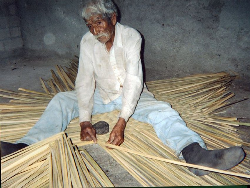 An artisan weaves a reed mat using only a stone and a metal knife.