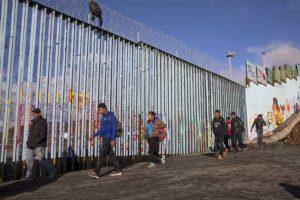 Migrants at the border fence near Tijuana.