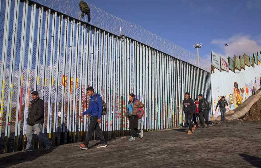 Migrants at the border fence near Tijuana.
