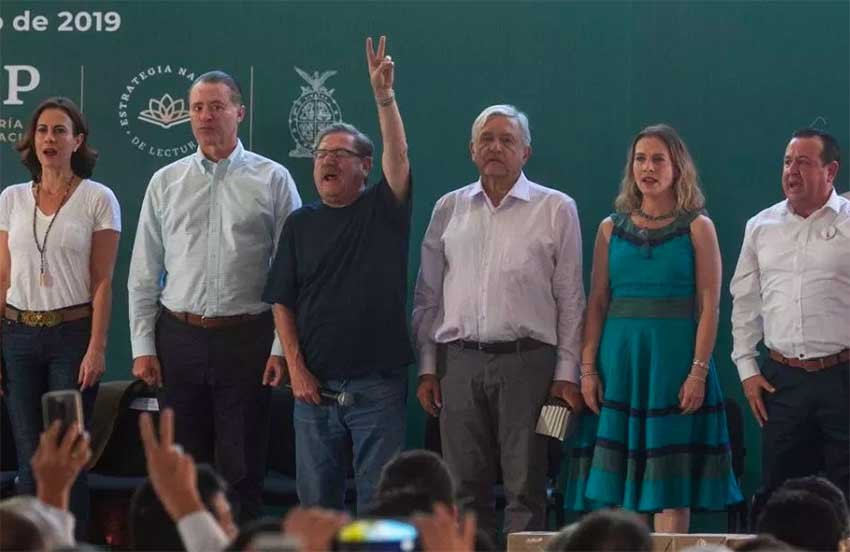 Taibo (arm raised) next to AMLO and Gutiérrez at launch of reading strategy.