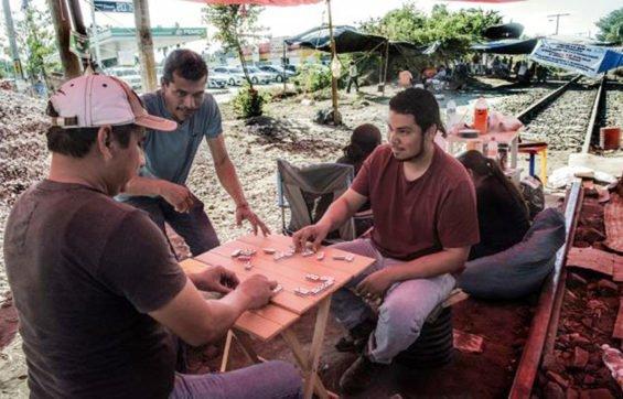 Michoacán teachers enjoy a game of dominoes on the railroad tracks.