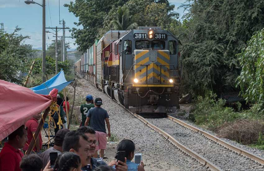 A train rolls in Michoacán but teachers maintain a vigil to the side of the tracks.