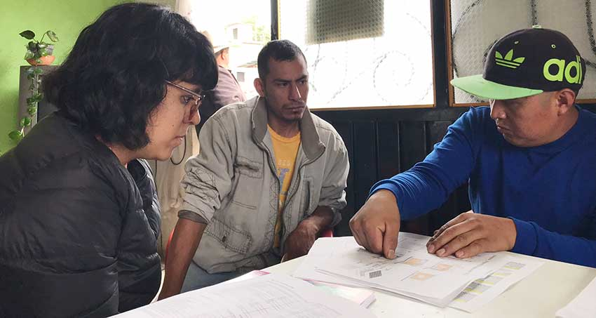 Solano, left, and Noé Lucas, right, discuss plans for an adobe home with Jorge Flores.