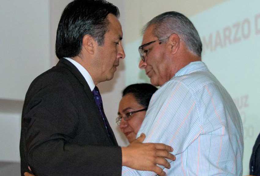 Governor García, left, and parent Benítez embrace during yesterday's ceremony.