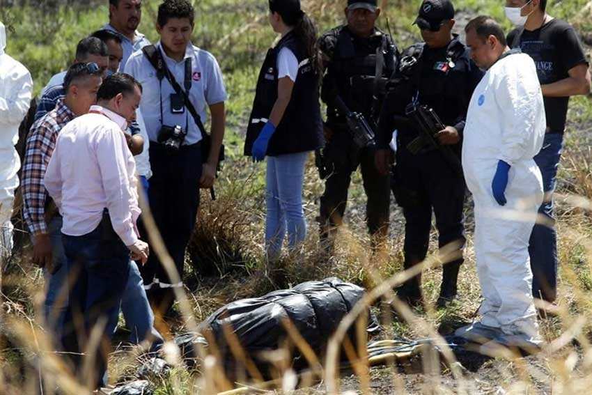 Officials inspect one of the 19 bags containing bodies.