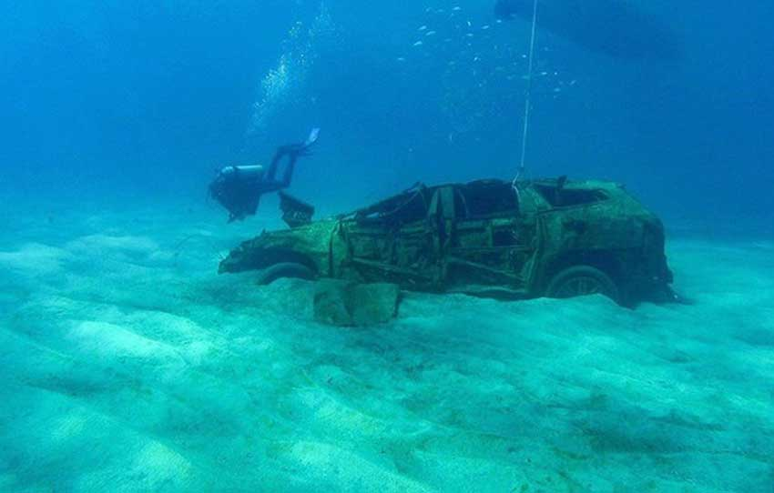 A diver swims near one of the eight vehicles at the bottom of Cabo San Lucas bay.