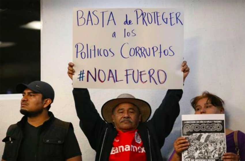 'No more protection for corrupt politicians,' reads the sign of a supporter of eliminating the fuero.