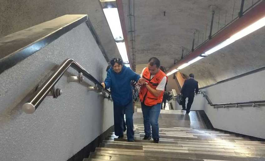A subway worker provides assistance to a Metro passenger.