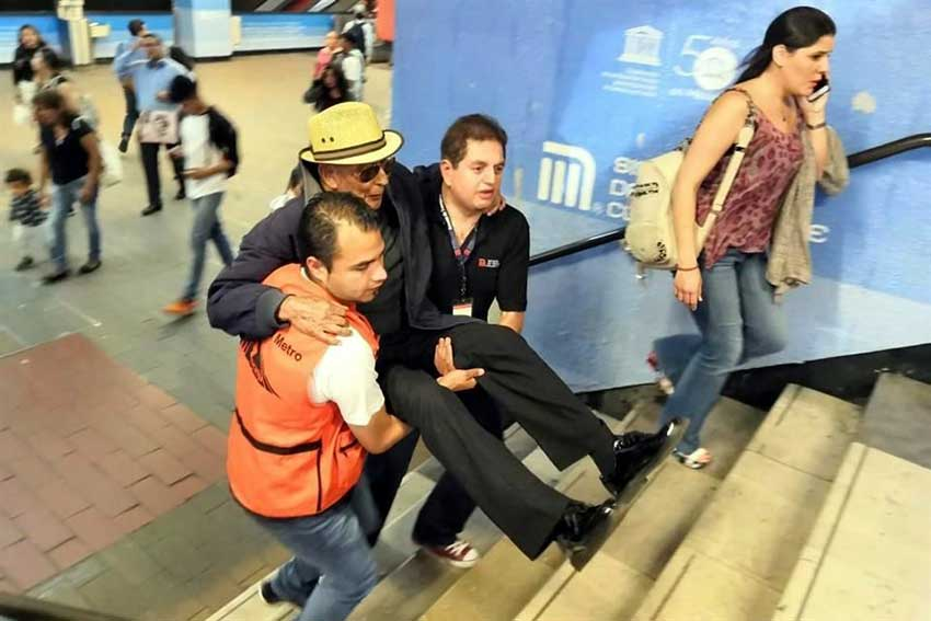 Metro staff carry a subway user up the stairs in Mexico City.