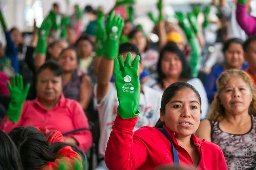 Domestic workers at a rally for better pay and benefits. The green glove is a symbol of the movement.