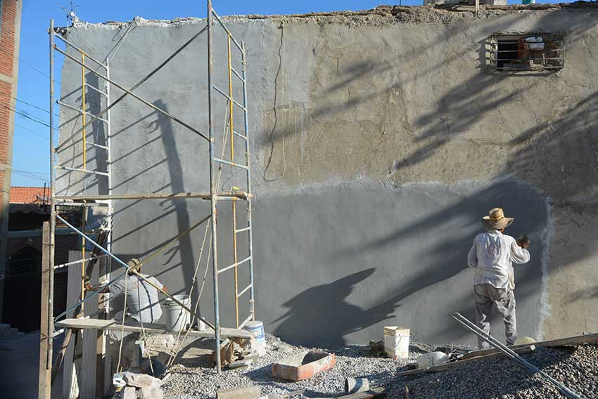 Plastering an exterior wall.