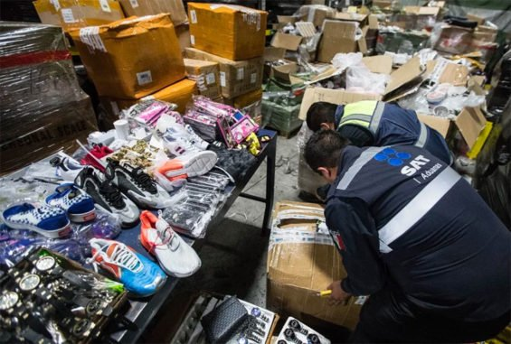 Customs agents inspect goods seized at Mexico City airport.
