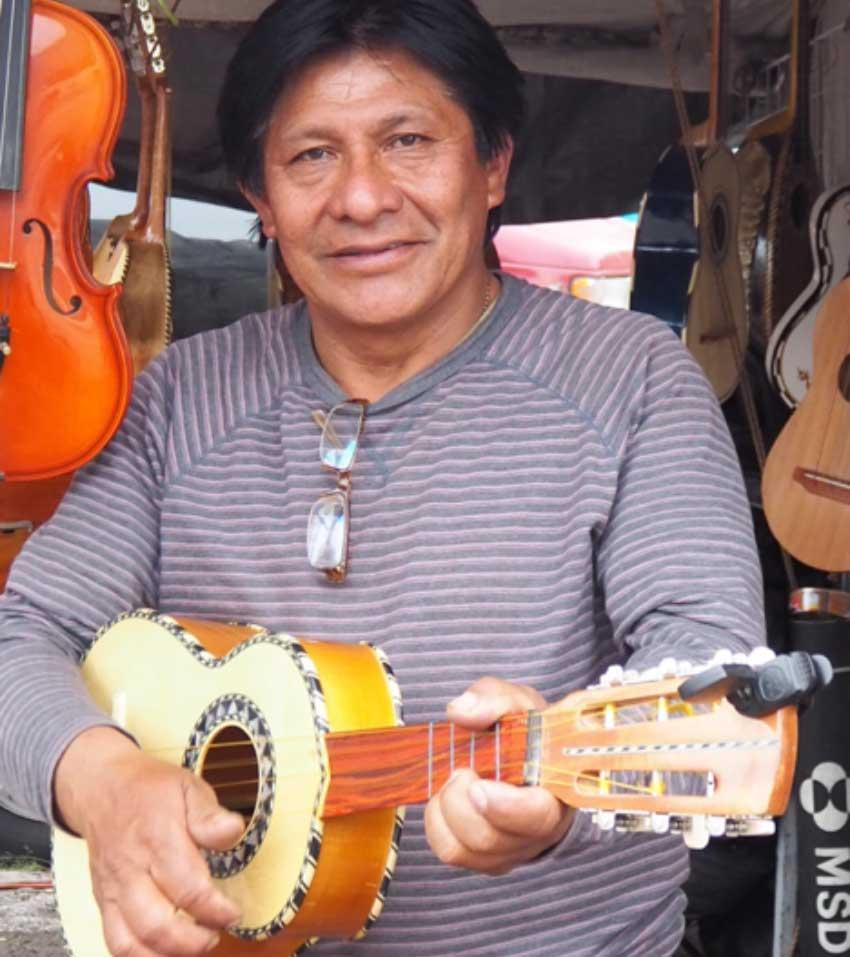 Jorge Rodríguez strums one of the vihuelas he has for sale.