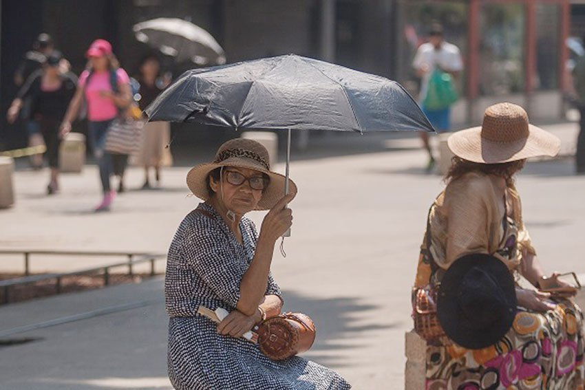 A woman shades herself from the sun in Mexico City, where more hot weather is in the forecast.