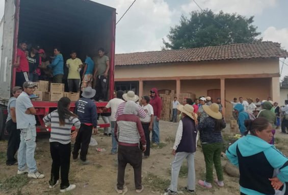 Rather than loot the goods, residents form human chain to load spilled contents in truck.
