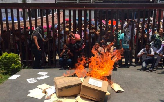 Guerrero teachers burn documents while vandalizing government buildings.