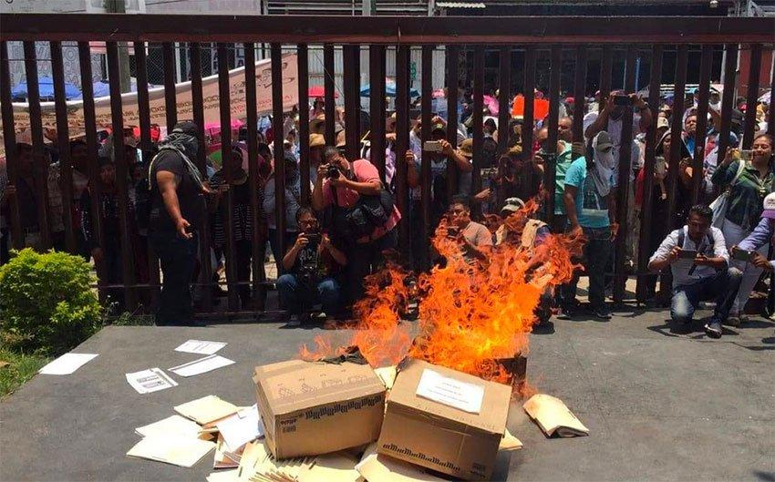 Guerrero teachers burn documents while vandalizing government buildings.
