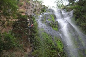 Father and daughter abseiling together at Nameless Falls.