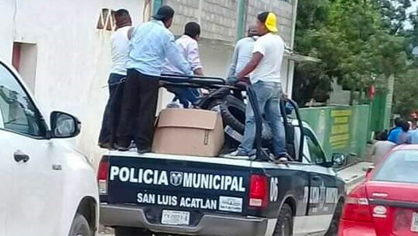 Angry citizens make off with a police vehicle.