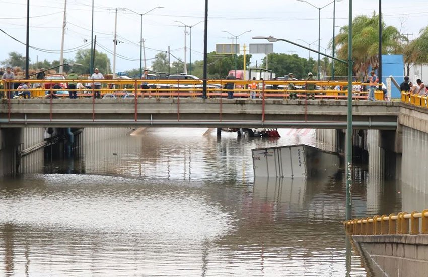 A truck is almost completely submerged below an overpass in León.