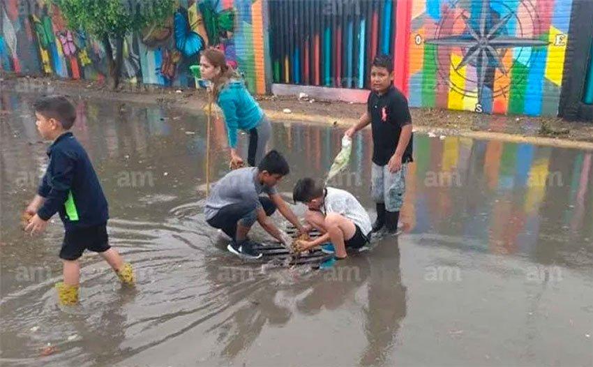 Children clear a plugged drain on a León street.