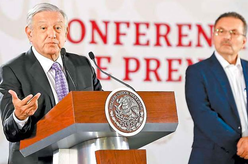 López Obrador speaks at his morning press conference as Pemex CEO Romero looks on.