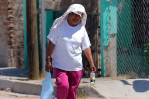 A woman covers up against high temperatures in Hermosillo.