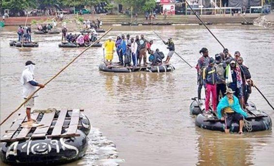 Rafts ferry migrants across the Suchiate river at the Mexico-Guatemala border.