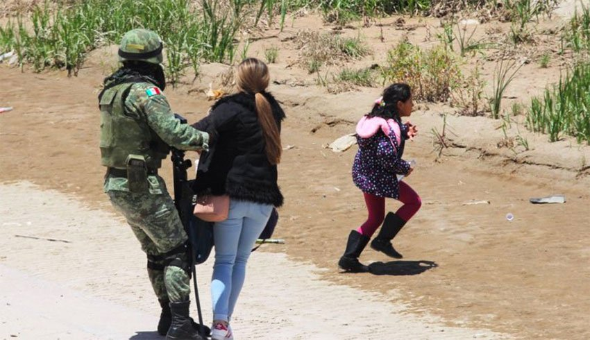 A soldier holds on to a woman while a girl appears to make a run for it.